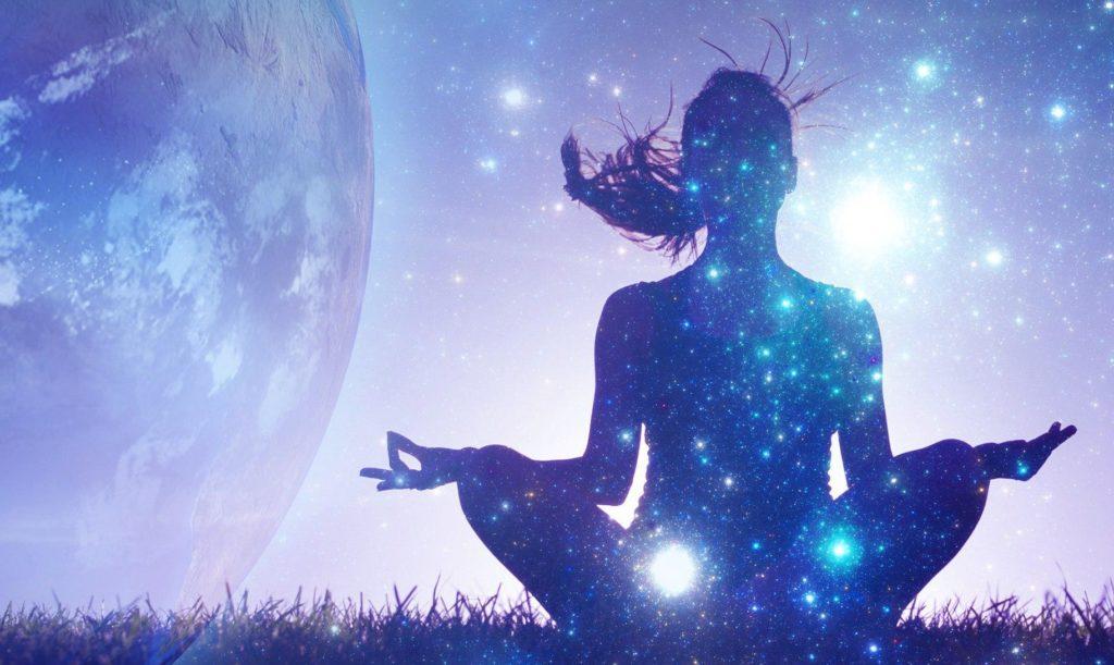 Девушка, сидящая в позе лотоса на фоне космоса